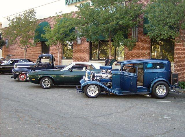 hot rods parked against brick building